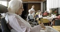 Residents sitting in the dining hall drinking coffee at a nursing home